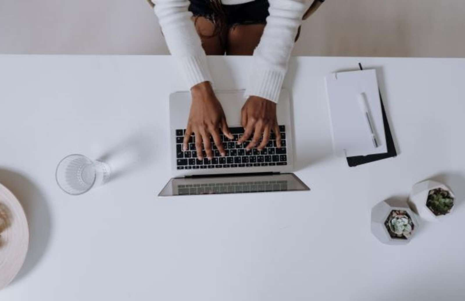 Aerial view of white table top with person's hands on a laptop keyboard