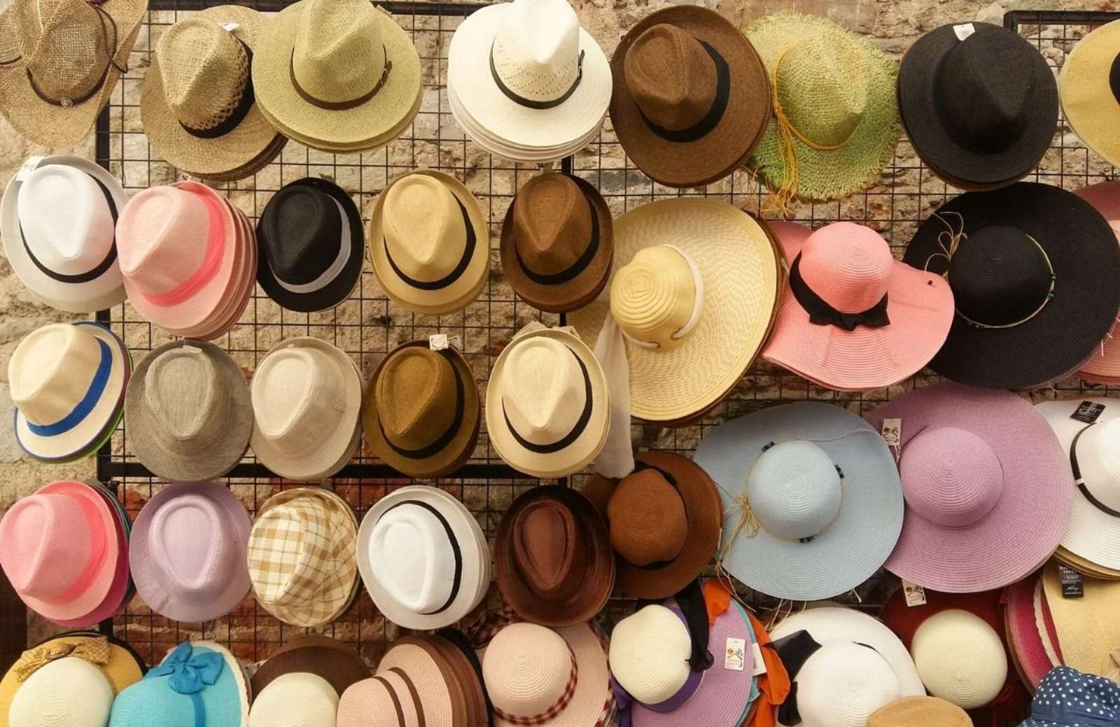 Wall covered with hats in various colors