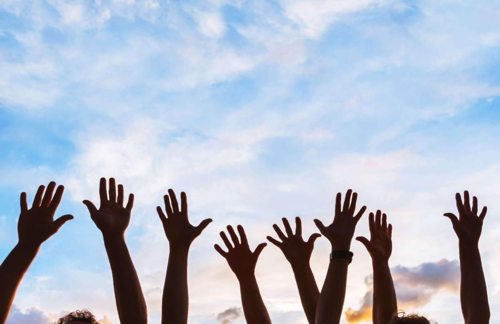 Raised arms and hands against a blue sky