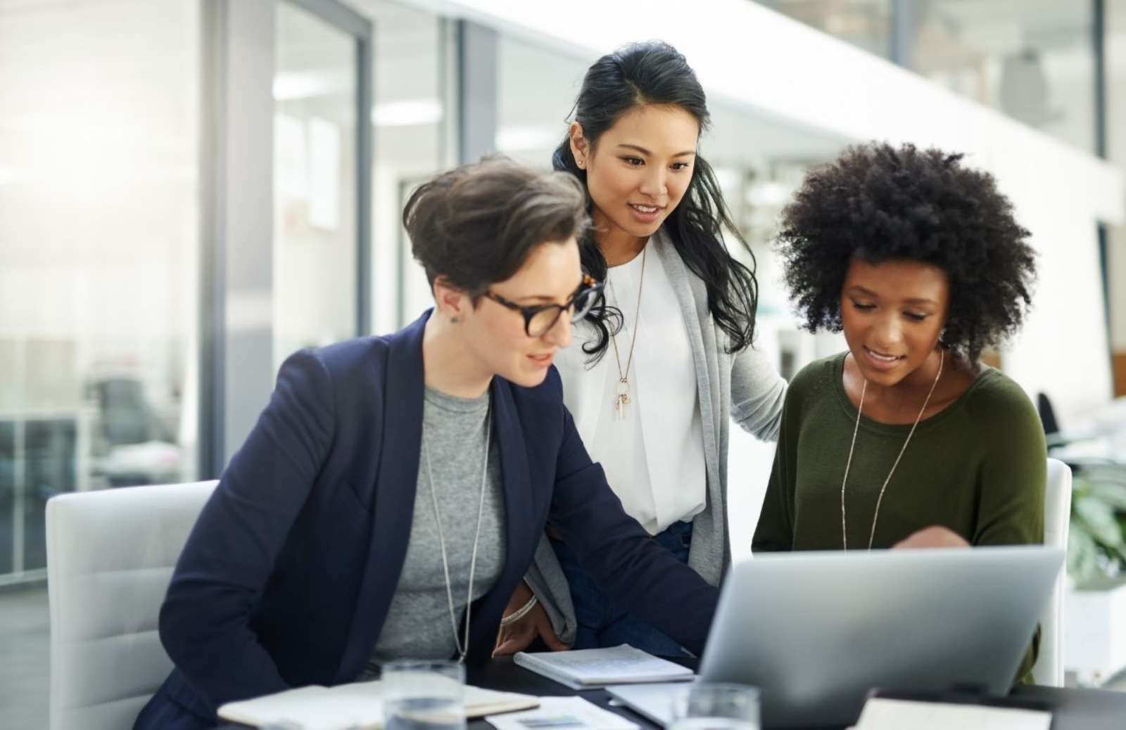 Three diverse women collaborating in office setting diversity in the workplace