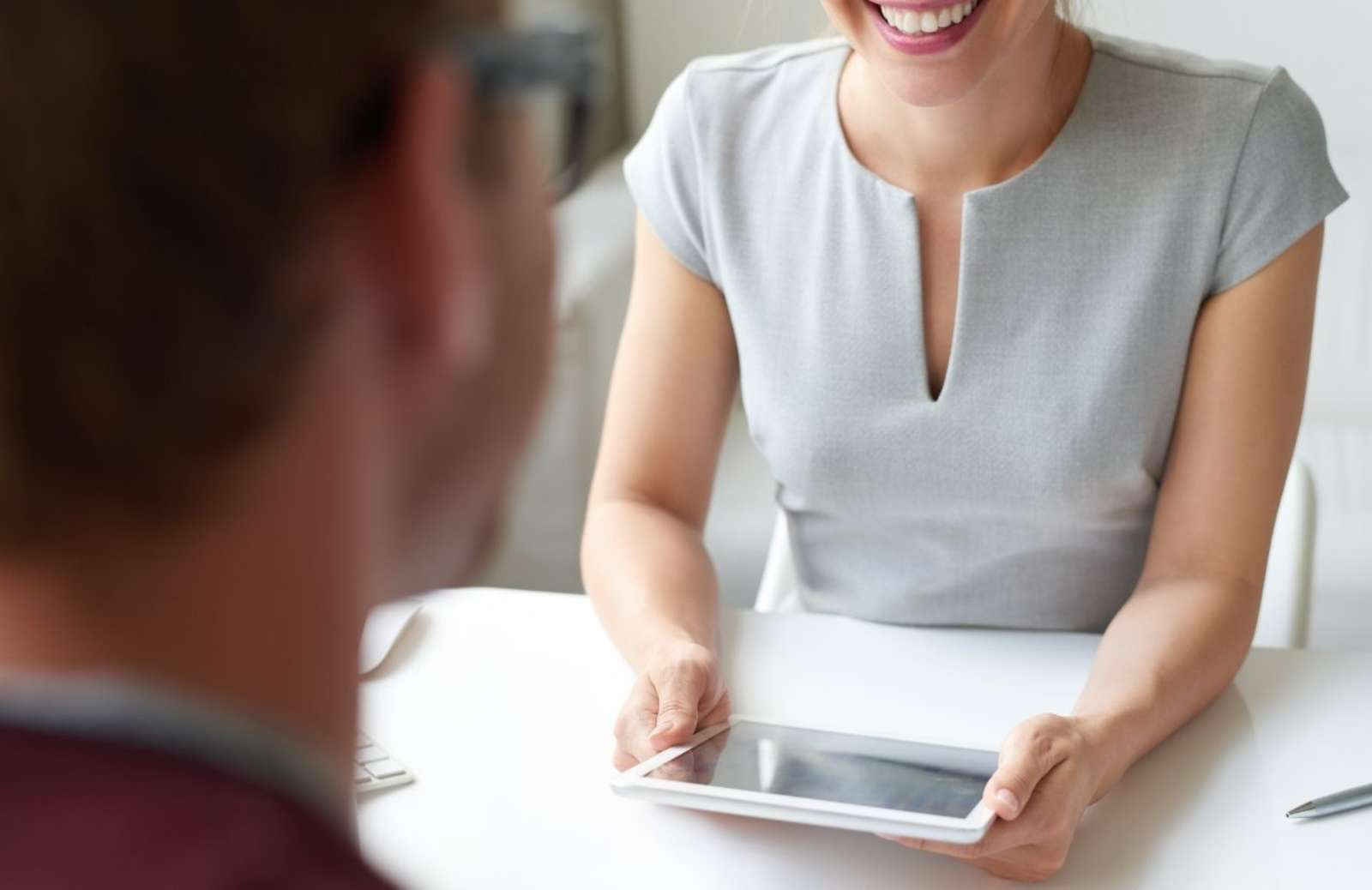 Woman holding tablet sitting across desk from man
