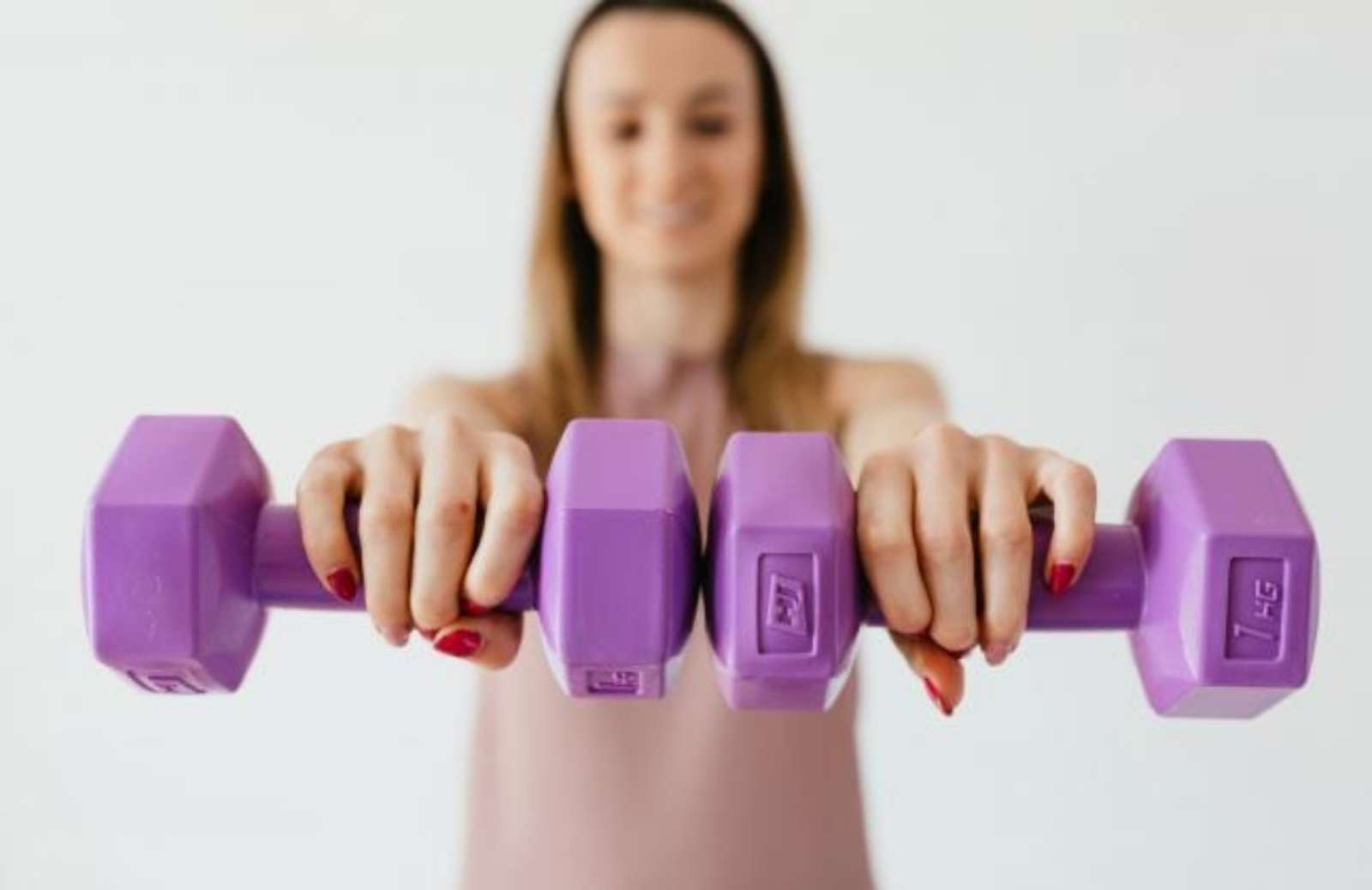 Woman holding two purple handweights in outstretched hands