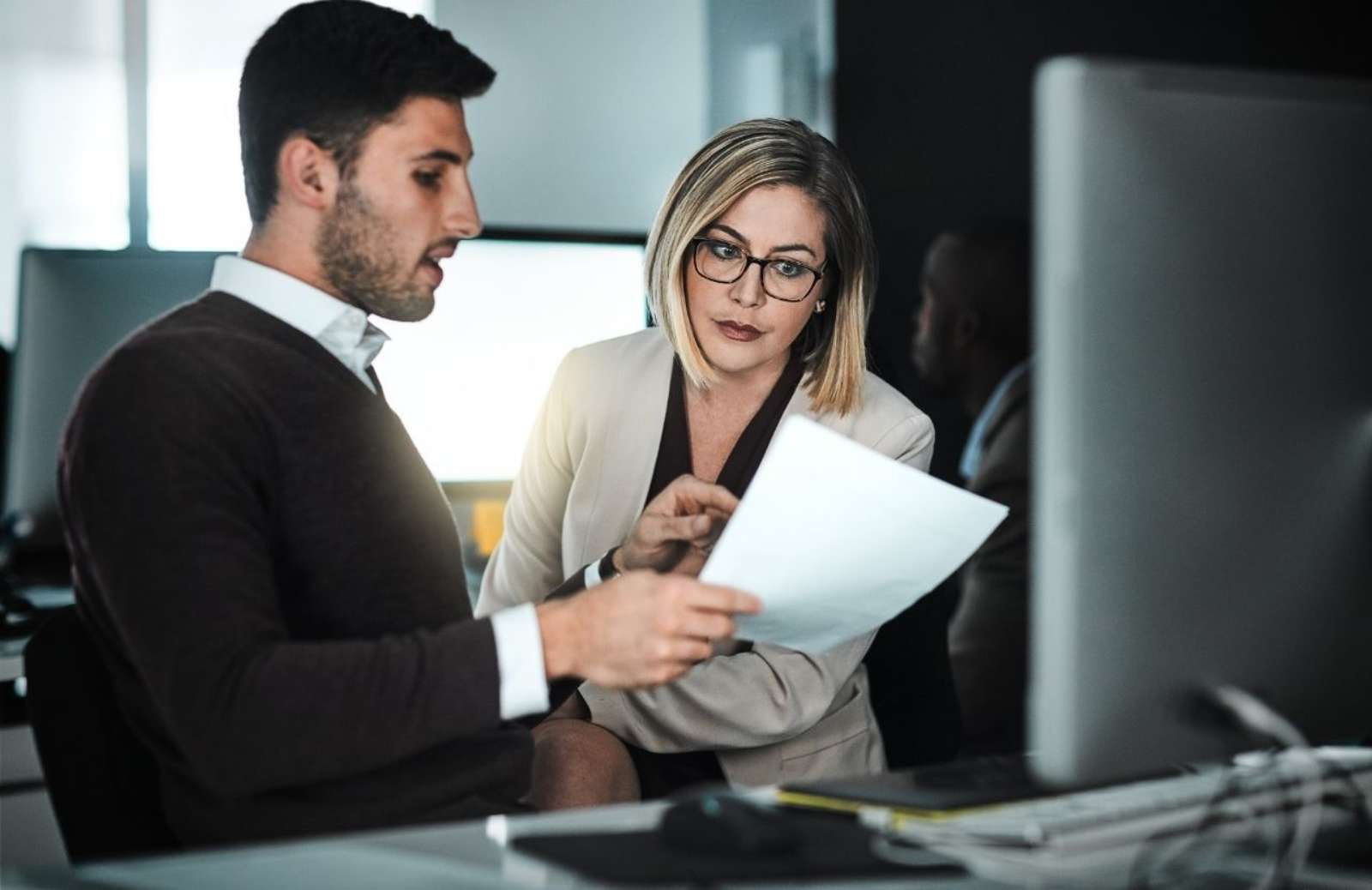 Business man showing a document to business woman