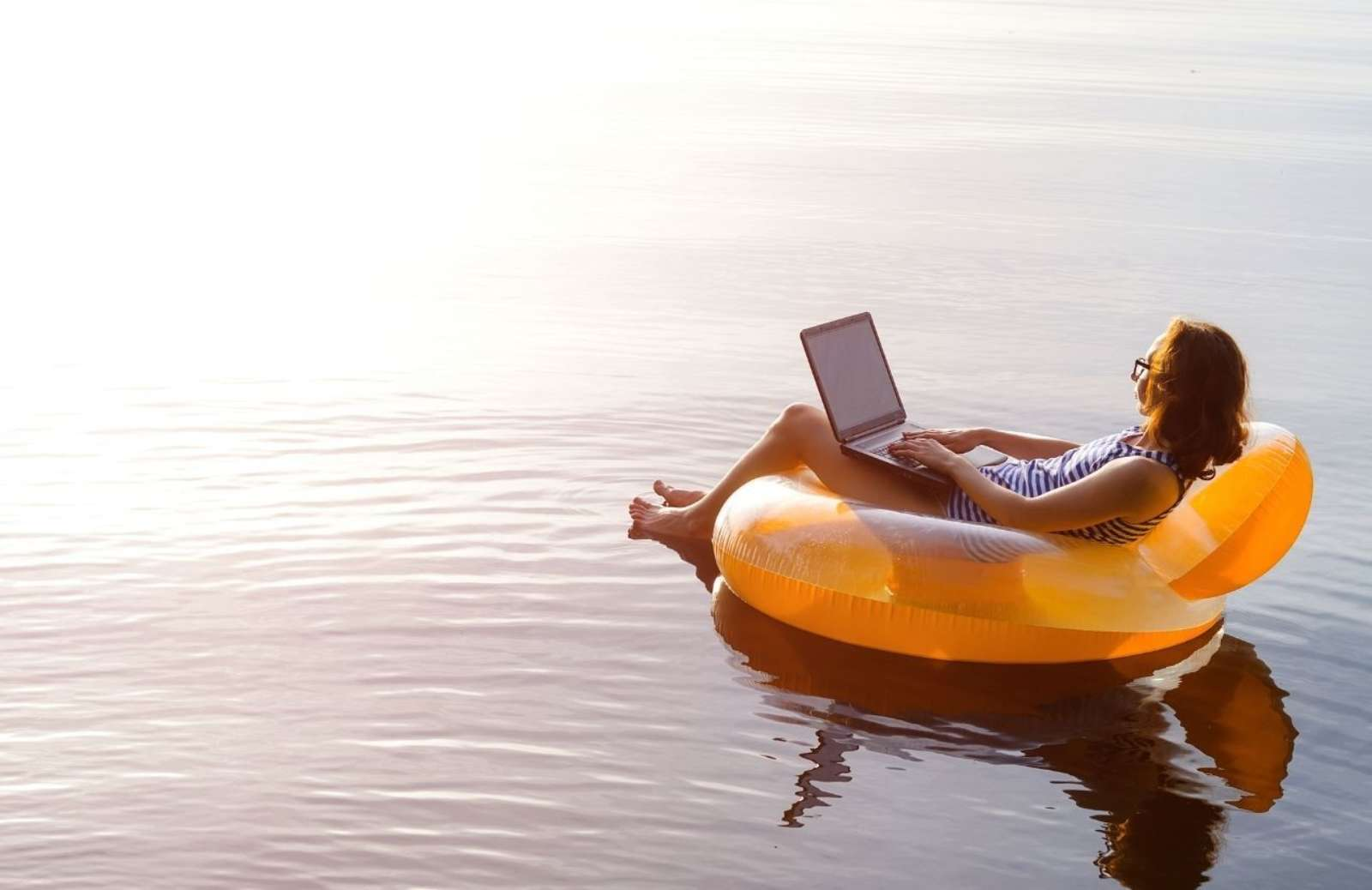 Person looking at laptop which sitting on inflatable chair floating on body of water