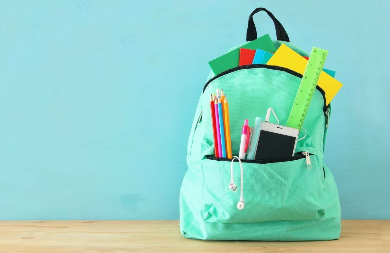Green backpack filled with school supplies on desk