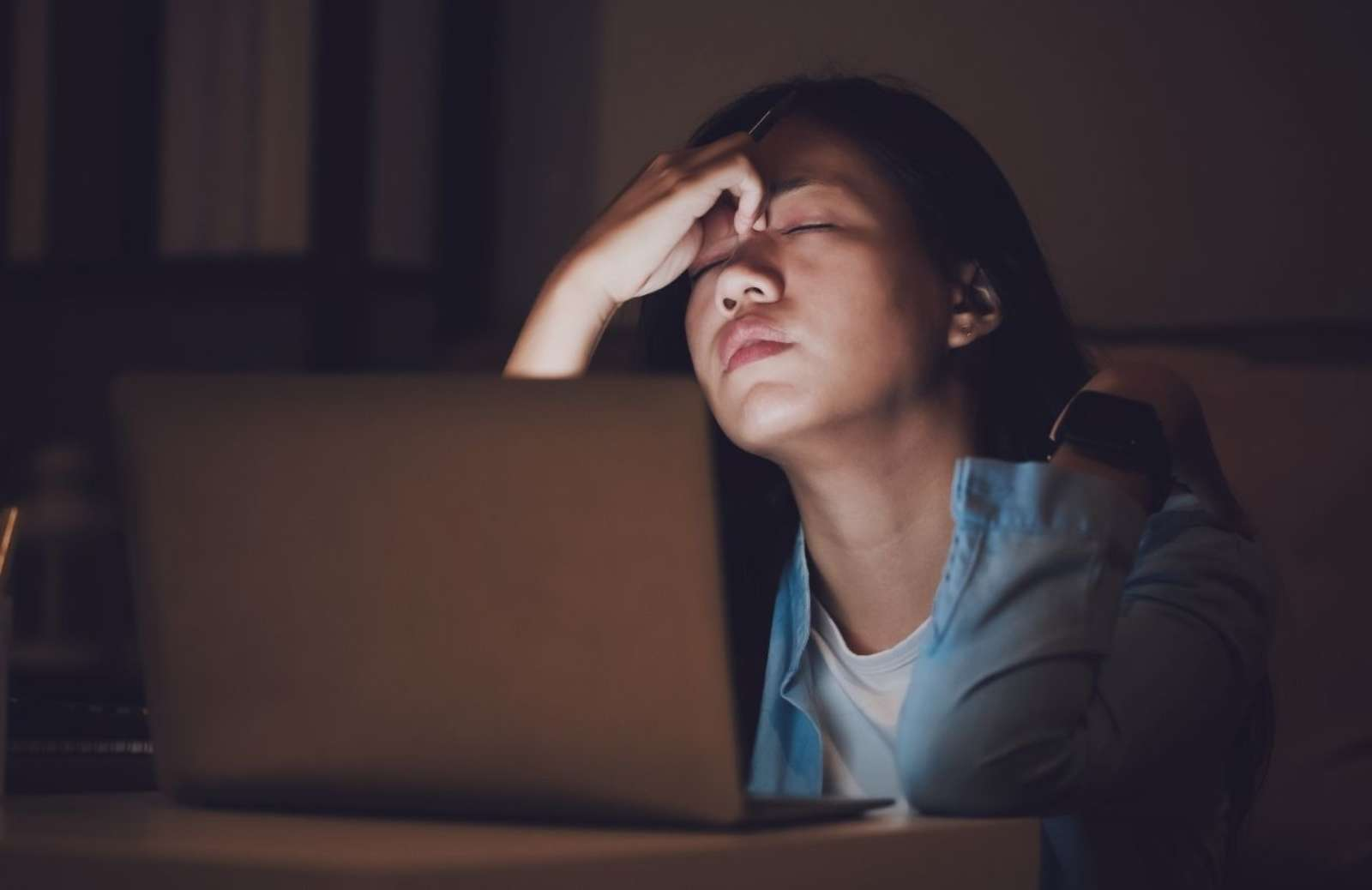 Tired woman rubbing her forhead while sitting in front of laptop