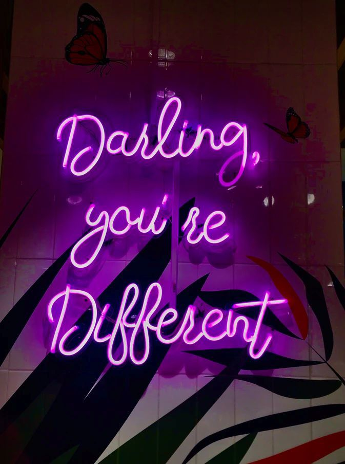 A purple neon sign in script lettering says