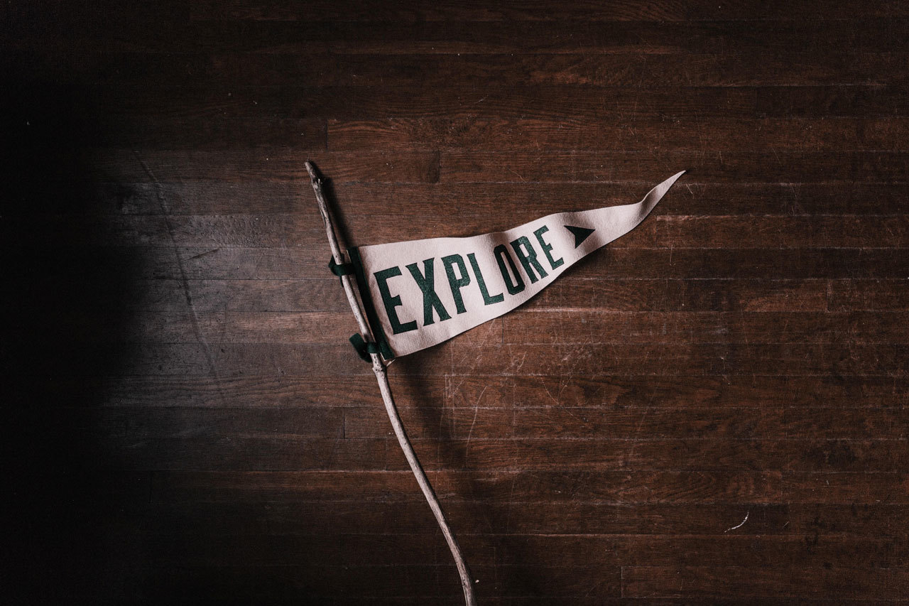 """A small white triangular flag has the words """"Explore"""" in black lettering, attached to a small stick. The flag is laying on a wood grain table."""