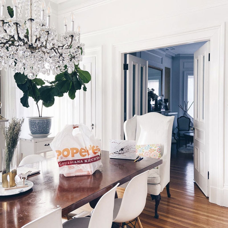 Kellie Van's beautifully white dining room with a crystal chandelier and a bag of Popeyes takeout on the wooden table