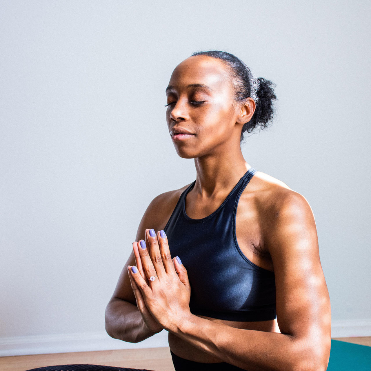 Woman wearing a black sports bra with her palms together in front of her chest and her eyes closed