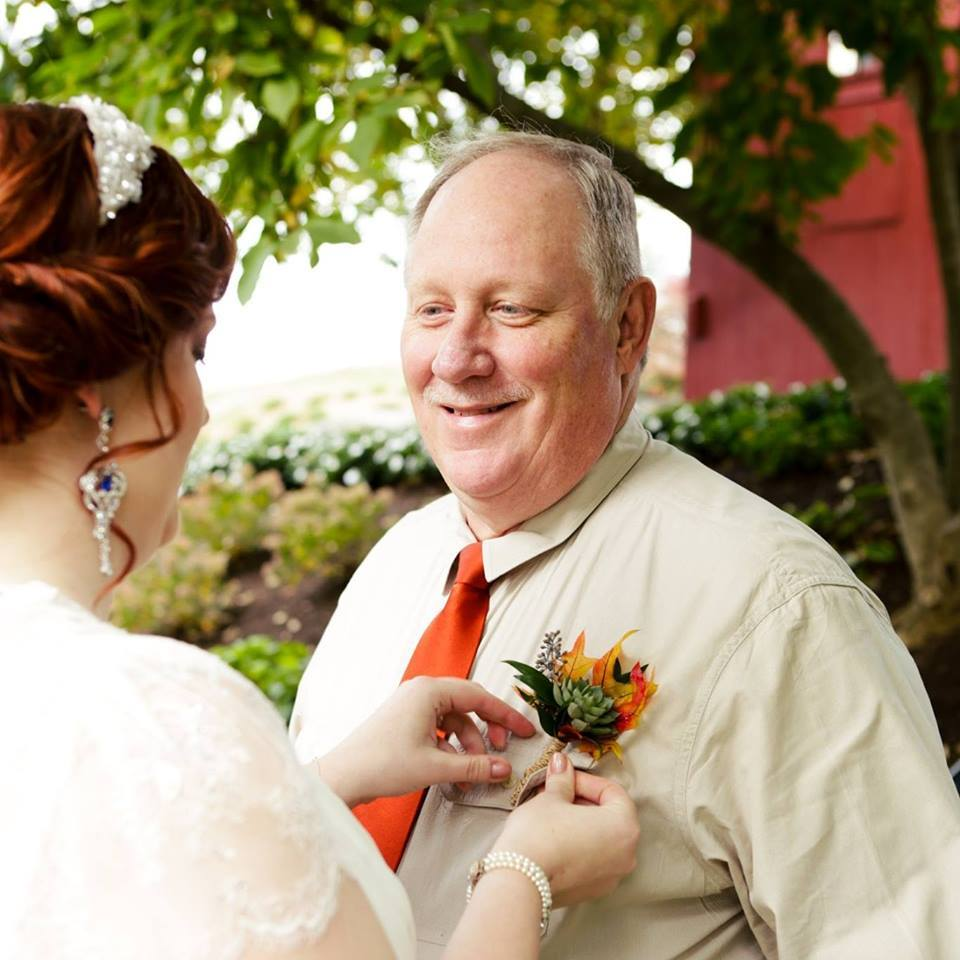 Shannon Amspacher pinning a boutonniere on her father on her wedding day