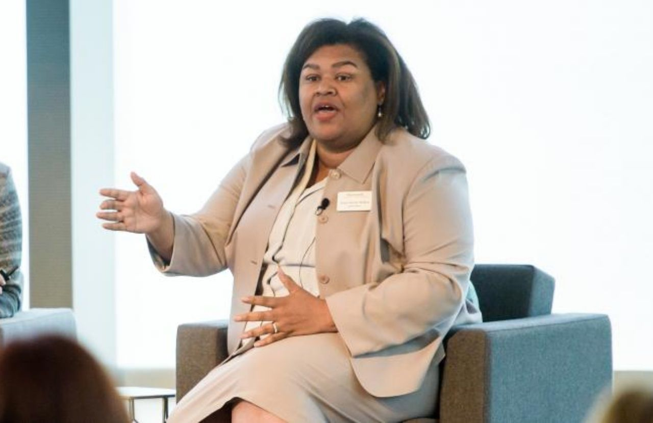 Cheryl McGee Wallace dressed in a light grey suit sitting on a teal armchair addresses the audience at the 2019 Chicago iRelaunch Return to Work Conference. Cheryl is gesturing with her right hand.