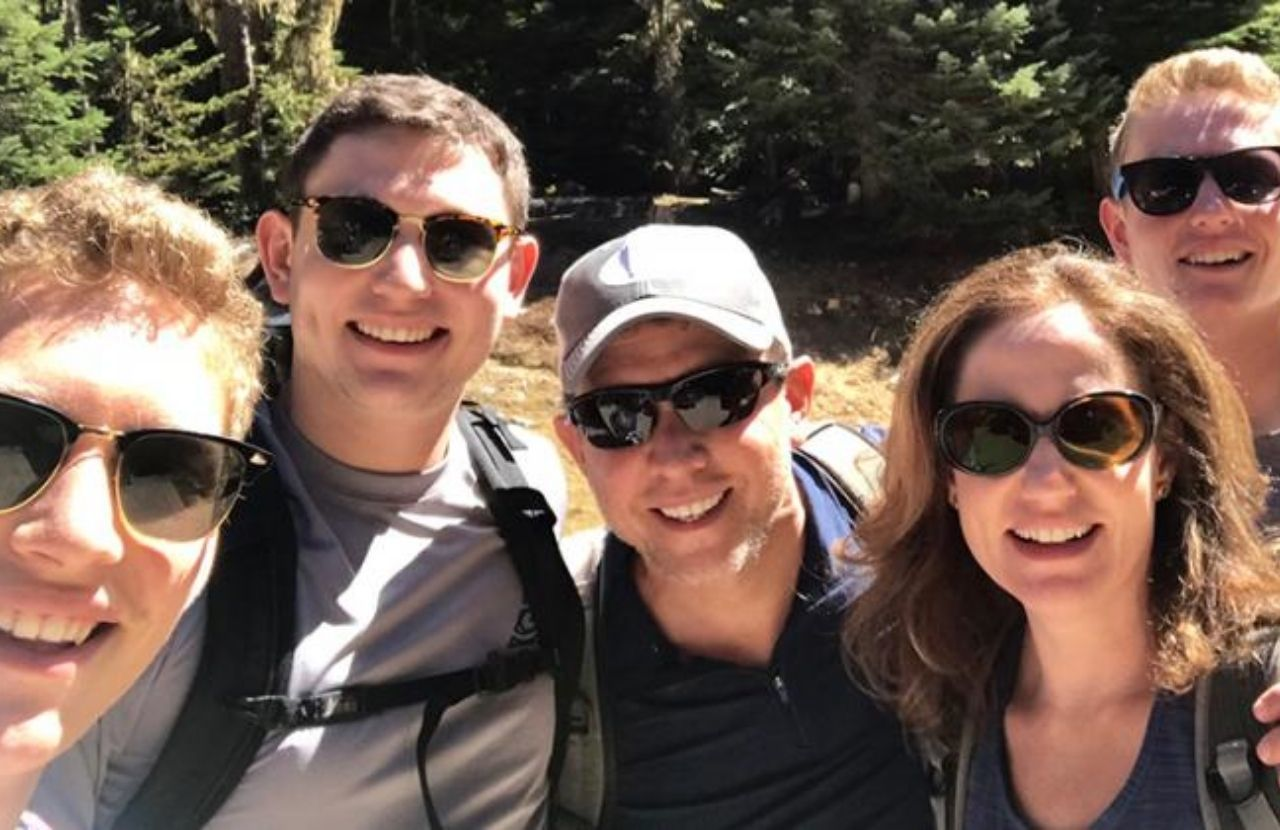 Michelle Friedman's family, all donning sunglasses smile with the woods in the background