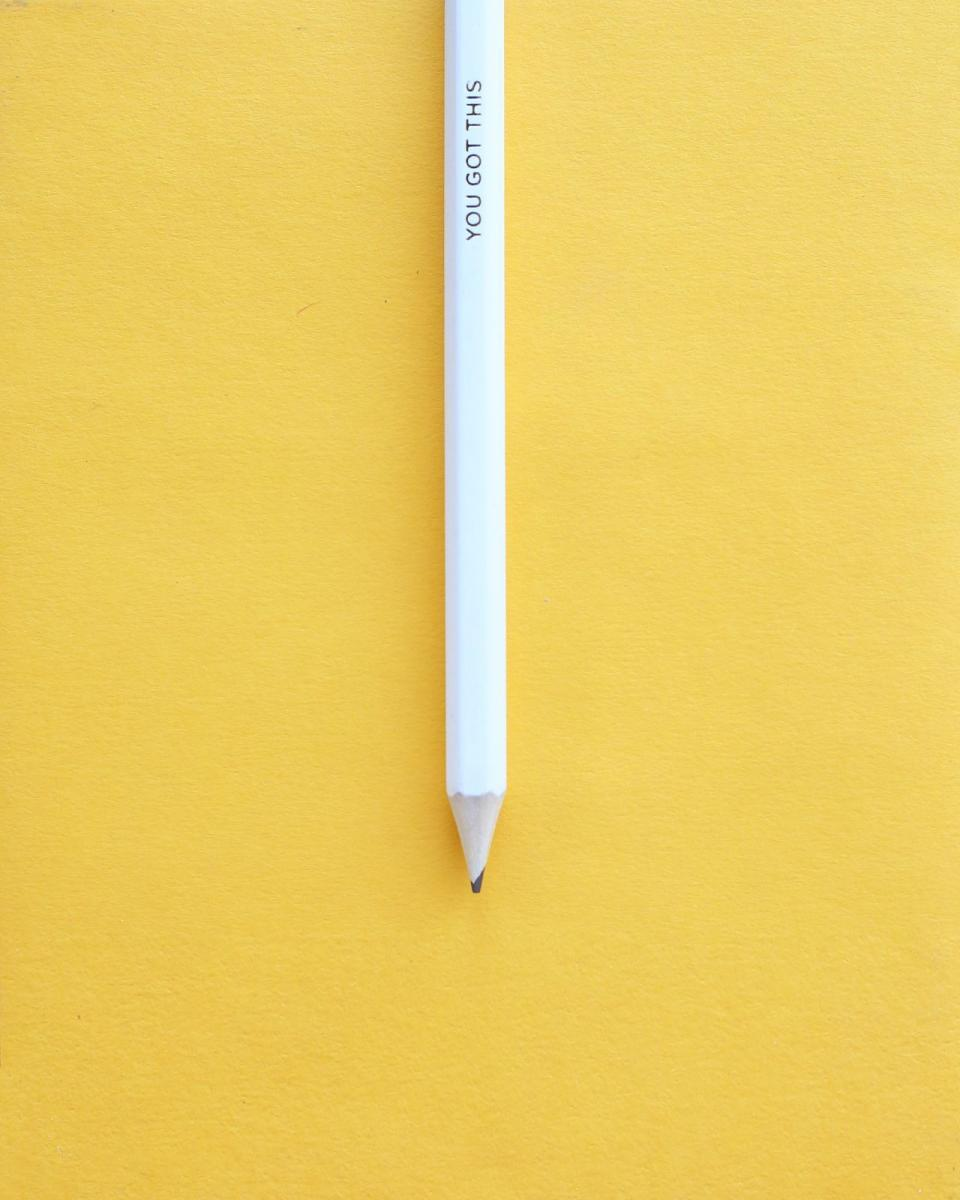 A sharpened white pencil with the words